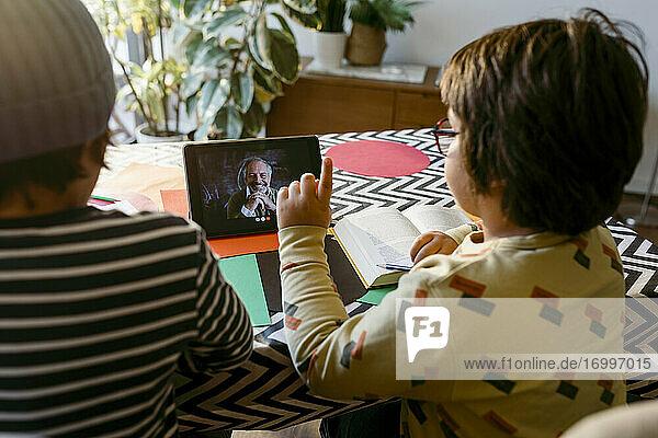 Junge im Grundschulalter  der beim E-Learning per Videoanruf mit einem männlichen Freund im Wohnzimmer sitzt Junge im Grundschulalter, der beim E-Learning per Videoanruf mit einem männlichen Freund im Wohnzimmer sitzt