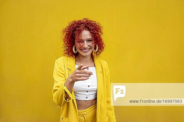 Glückliche junge Frau mit rotem lockigem Haar  die mit dem Finger vor einer gelben Wand zeigt Glückliche junge Frau mit rotem lockigem Haar, die mit dem Finger vor einer gelben Wand zeigt