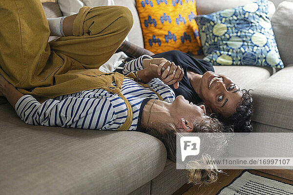 Woman holding girlfriend hand while lying on sofa at home