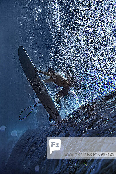 Male surfer surfing on surfboard undersea at Maldives