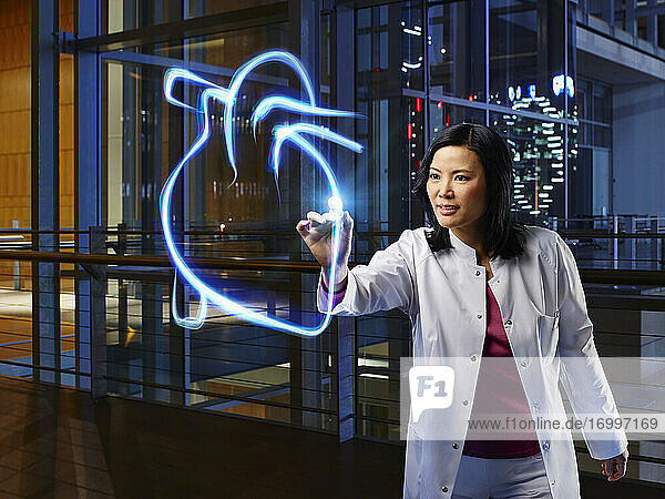 Female specialist light painting heart in laboratory at hospital