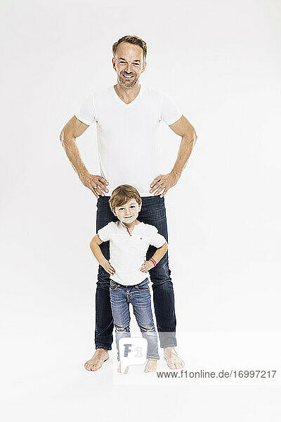 Happy man with cute son standing with hands on hip against white background