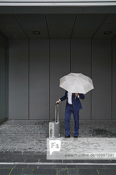 Businessman with luggage and umbrella standing on footpath