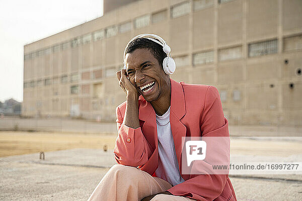 Man wearing headphones laughing while sitting against building