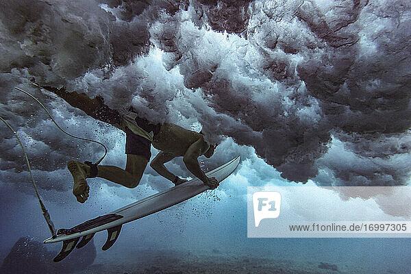 Männlicher Surfer auf dem Surfbrett beim Tauchen unter Wasser auf den Malediven Männlicher Surfer auf dem Surfbrett beim Tauchen unter Wasser auf den Malediven
