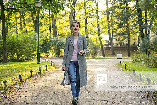 Happy businesswoman during autumn walking in park