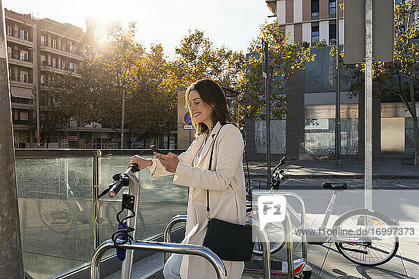 Businesswoman doing contactless payment while standing at bicycle parking station in city
