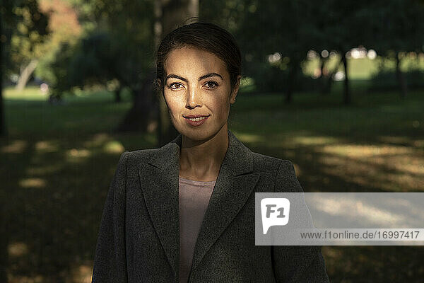 Young businesswoman standing in park during autumn