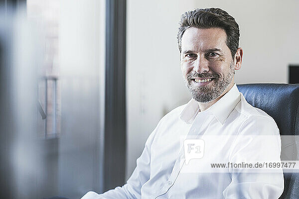 Confident businessman smiling while sitting on chair at office