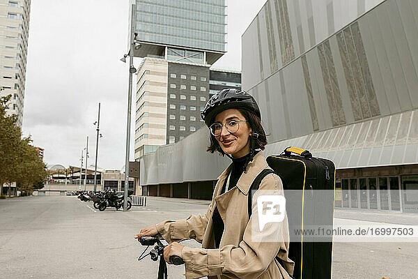 Musiker mit Instrumentenkoffer und Elektroroller lächelnd in der Stadt stehend Musiker mit Instrumentenkoffer und Elektroroller lächelnd in der Stadt stehend