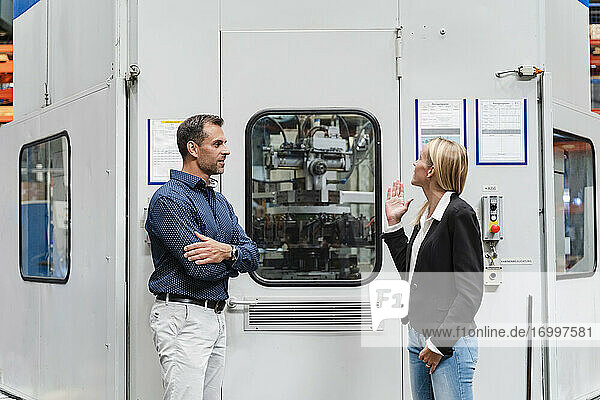 Businesswoman explaining male colleague while standing by control room in industry