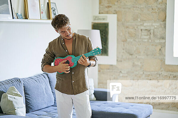 Male musician playing ukulele while standing in living room at home
