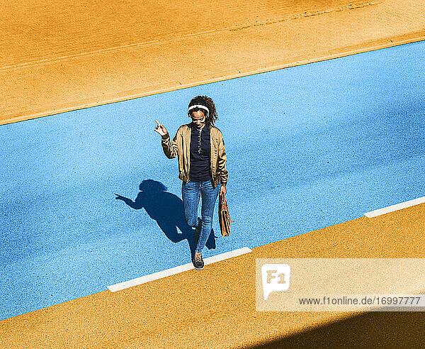 Junge Frau hört Musik über Kopfhörer  während sie an einem sonnigen Tag auf einer gelben und blauen Straße spazieren geht Junge Frau hört Musik über Kopfhörer, während sie an einem sonnigen Tag auf einer gelben und blauen Straße spazieren geht