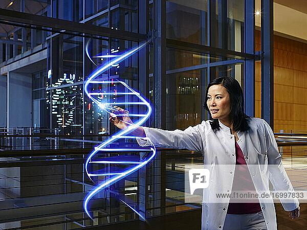 Reife Ärztin mit Lichtmalerei DNA im Labor im Krankenhaus Reife Ärztin mit Lichtmalerei DNA im Labor im Krankenhaus
