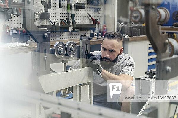 Professioneller männlicher Ingenieur  der sich bei der Prüfung einer Maschine in der Industrie konzentriert