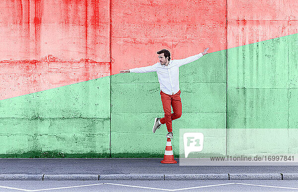 Carefree man standing on traffic cone against multi colored wall