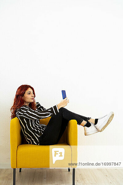 Young woman taking selfie through mobile phone while sitting on armchair at office