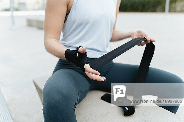 Sportswoman tying boxing wrap in hand while sitting on retaining wall