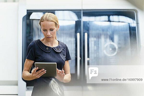 Blonde Geschäftsfrau  die ein digitales Tablet benutzt  während sie in einer Fabrik steht