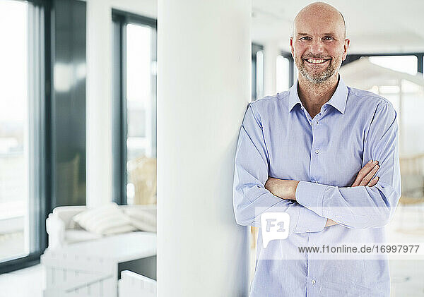 Entrepreneur smiling while standing with arms crossed at home