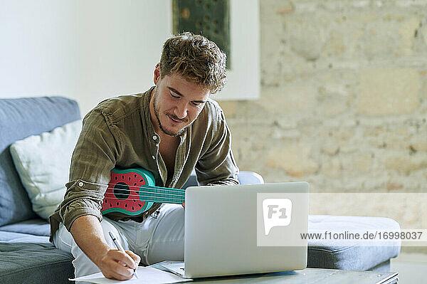 Man learning ukulele through laptop during online tutorial at home