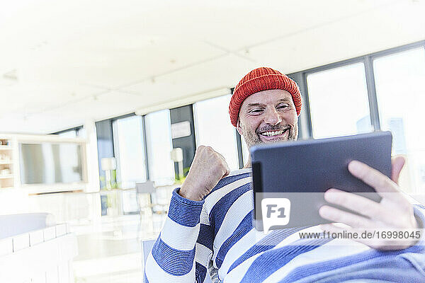 Happy man cheering while using digital tablet sitting at home