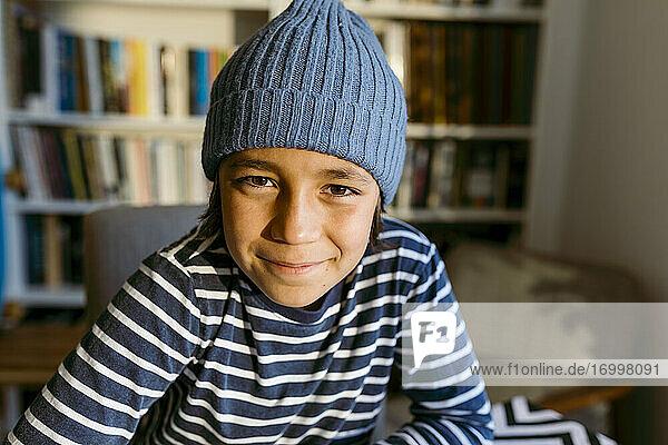 Lächelnder Junge mit Strickmütze zu Hause Lächelnder Junge mit Strickmütze zu Hause