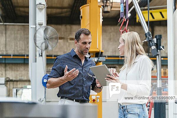 Geschäftsmann und weibliche Kollegin diskutieren bei der Nutzung eines digitalen Tablets in der Industrie