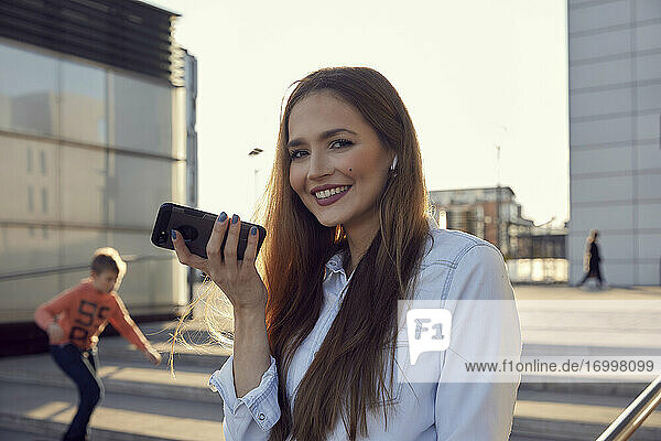 Businesswoman talking on mobile phone while standing with boy playing in background on steps
