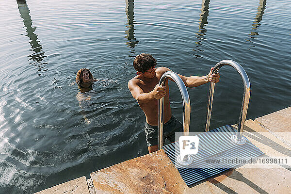 Young man getting out of the water onto a jetty