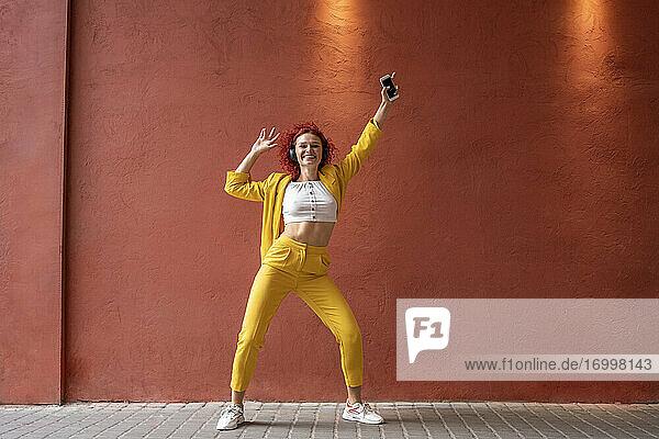 Junge Frau im gelben Anzug trägt Kopfhörer und tanzt zu Musik von ihrem Smartphone Junge Frau im gelben Anzug trägt Kopfhörer und tanzt zu Musik von ihrem Smartphone