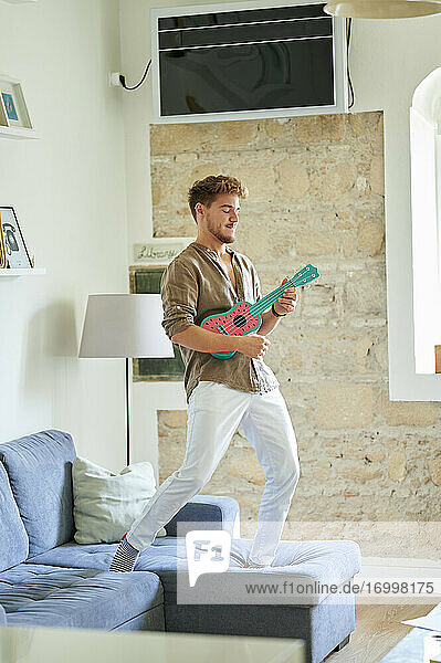 Man standing over sofa with ukulele in living room at home