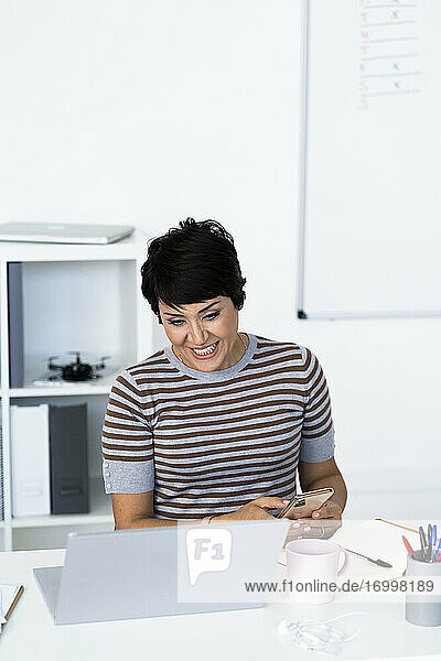 Portrait of businesswoman sitting at office desk with smart phone in hands