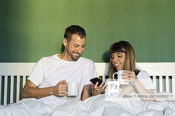 Smiling couple with coffee cup using mobile phone while sitting in bed at home