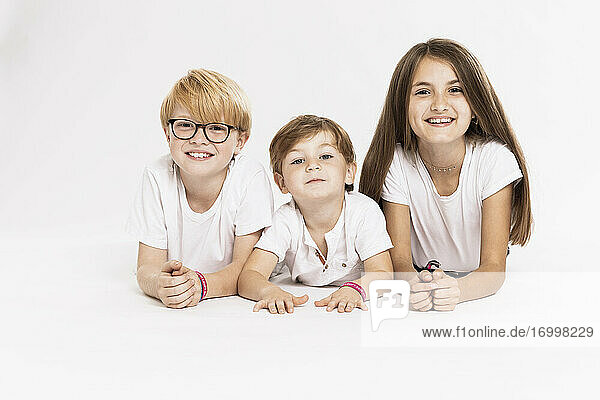 Smiling bothers and sister lying over white background