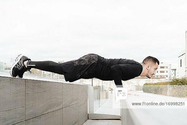 Young man doing push-ups on rooftop retaining wall