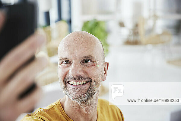 Mature man taking selfie through smart phone while standing at home