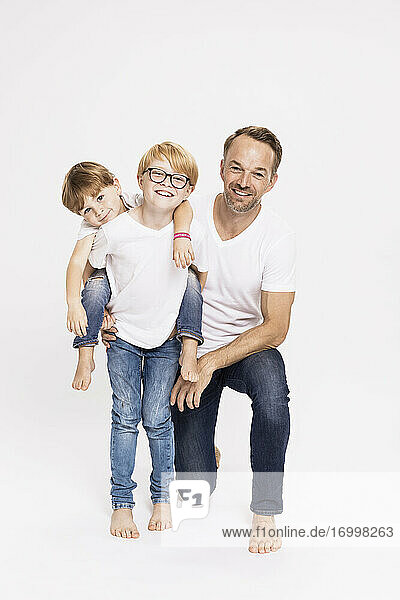 Boy piggybacking brother while standing by father against white background