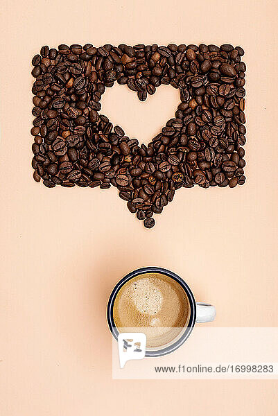 Roasted coffee beans arranged into shape of heart inside online chat bubble