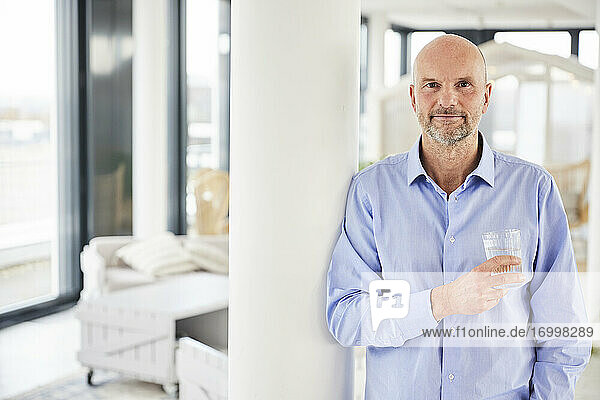 Businessman holding drinking glass while standing at home
