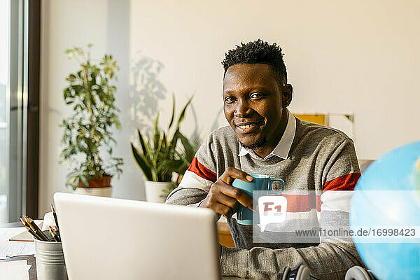 Lächelnder männlicher Unternehmer mit Kaffeetasse im Büro zu Hause Lächelnder männlicher Unternehmer mit Kaffeetasse im Büro zu Hause