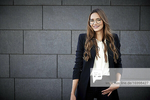 Smiling female entrepreneur standing with hands in pockets against brick wall