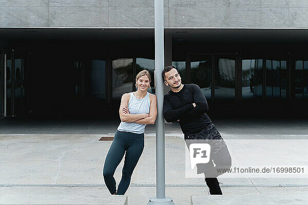 Smiling young couple leaning on pole