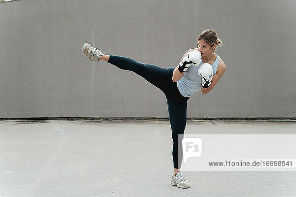 Woman with boxing glove practicing kickboxing against wall