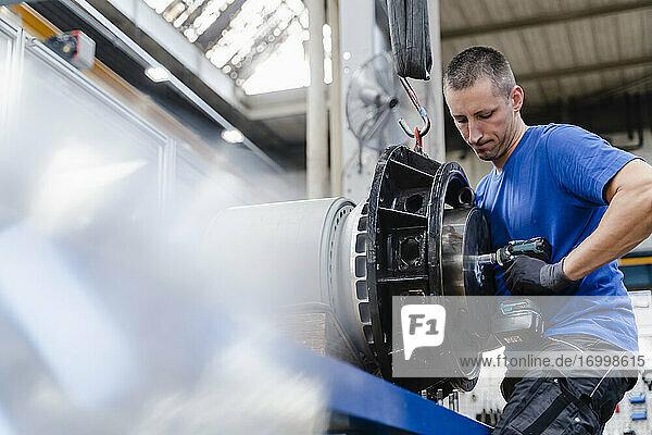 Männlicher Techniker  der eine Schraube mit Ausrüstung in der Industrie befestigt