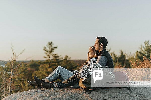 Junges Paar sitzt bei einer Herbstwanderung auf einem Felsen zusammen