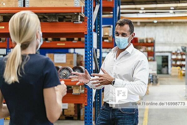 Geschäftsmann im Gespräch mit einer Kollegin in einer Fabrik während COVID-19