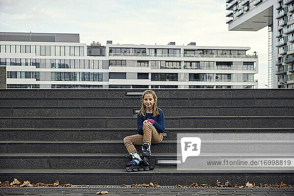 Girl wearing roller skate smiling while sitting on staircase in city