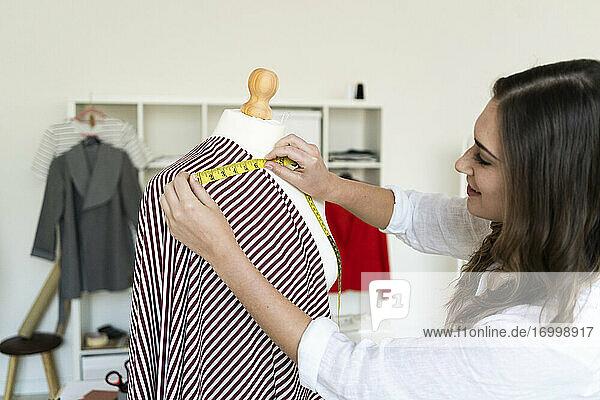 Young female designer measuring fabric mannequin at studio