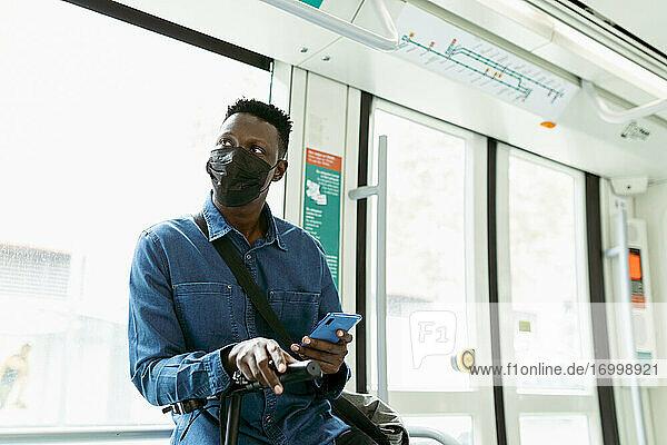 Afrikanischer Geschäftsmann mit Gesichtsschutzmaske während der Fahrt im Zug Afrikanischer Geschäftsmann mit Gesichtsschutzmaske während der Fahrt im Zug